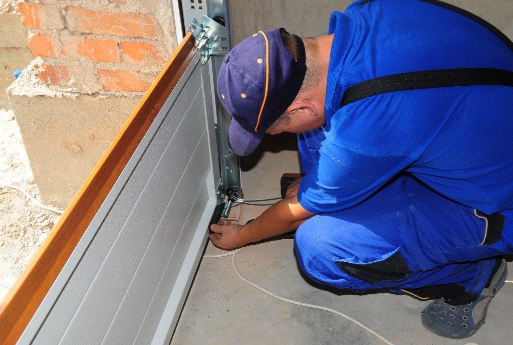 Man Checking Garage Door Springs