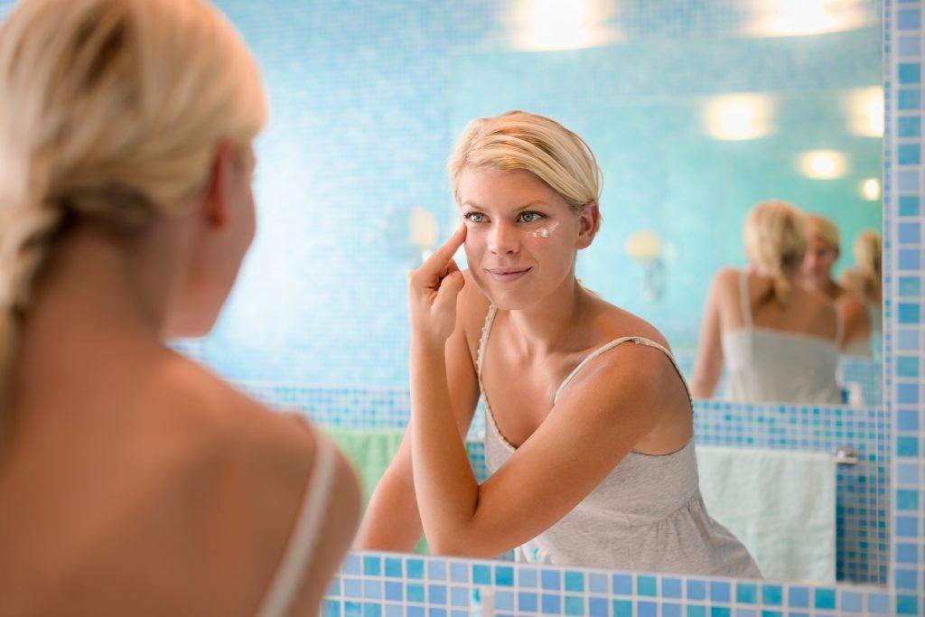 Woman putting cream under eyes