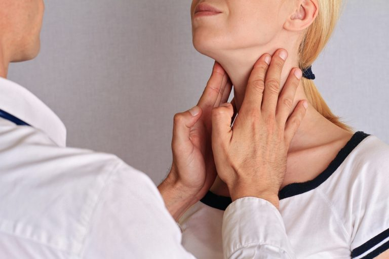 Doctor checking patient neck