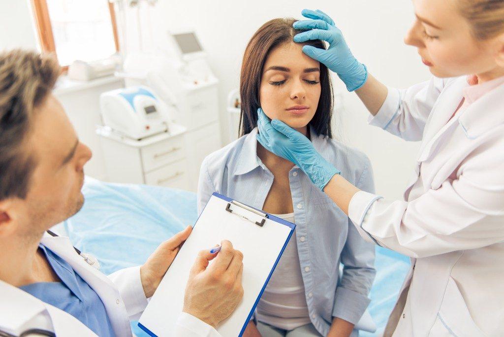 Plastic surgeon examining face