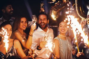 group of people drinking wine and lighting fireworks