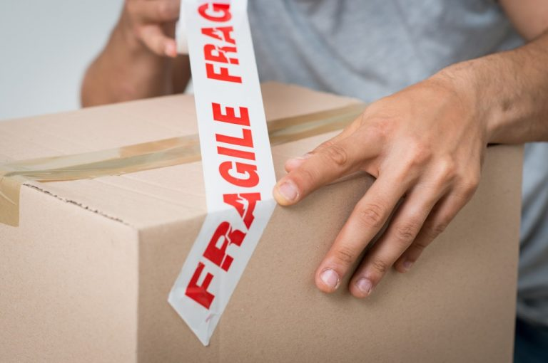 fragile tape being used over a packed box