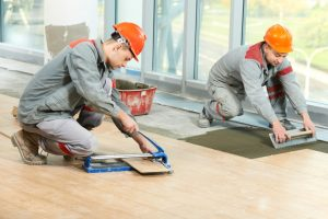 workers installing floor tiles