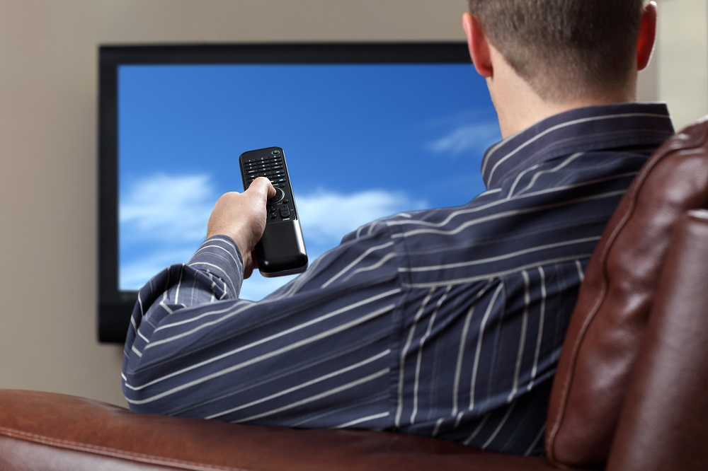 man sitting down focused on the tv