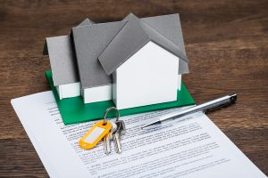 a miniature house and keys on top of a document