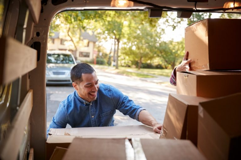 smiling man getting boxes from his car to his new home