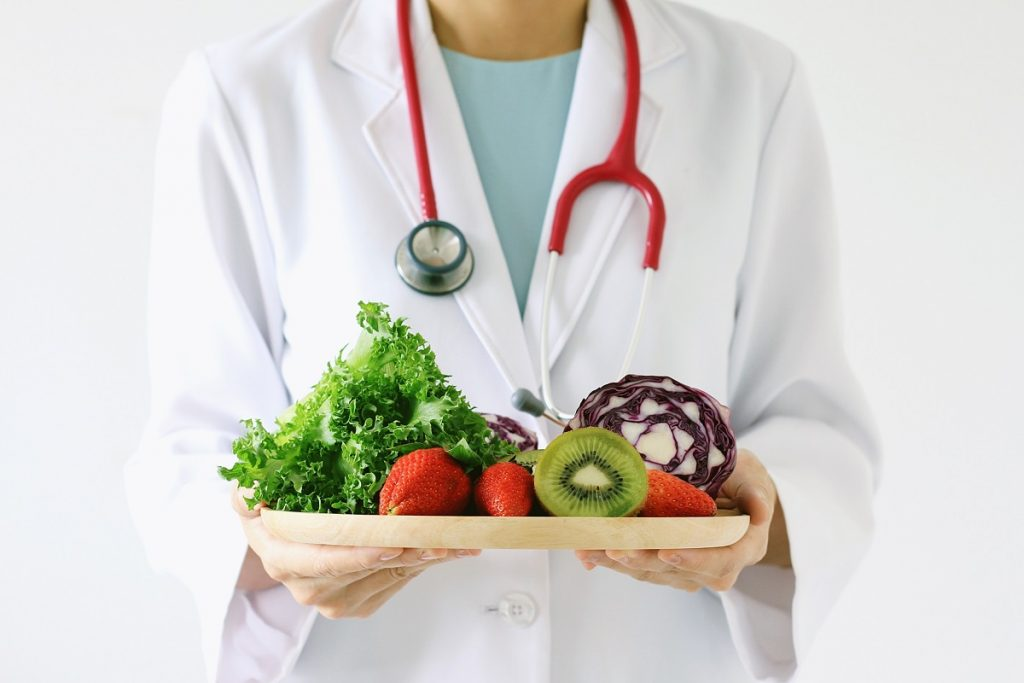 Doctor holding tray of fruits and vegetables