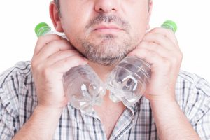 Man cooling his neck using cold water bottles