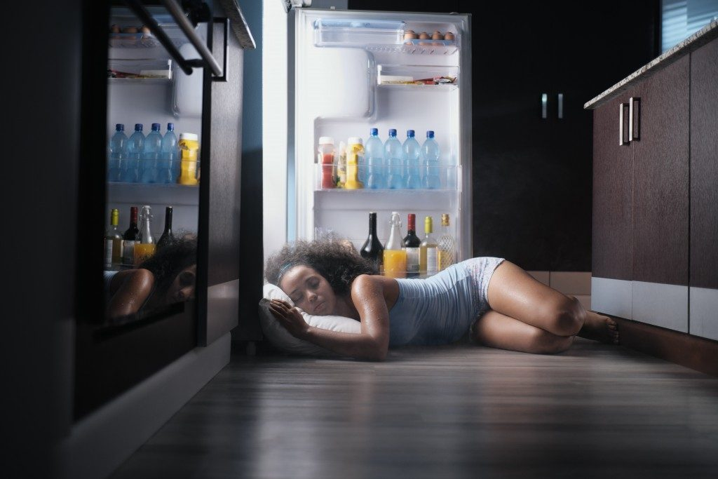 sleeping by the refrigerator