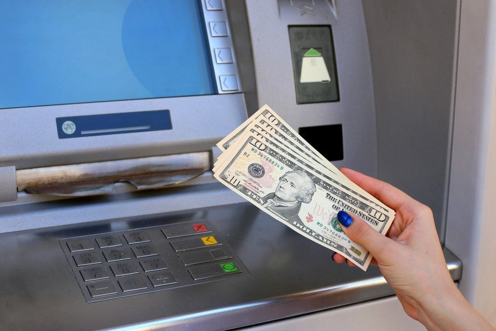 dollar banknotes in front of the atm