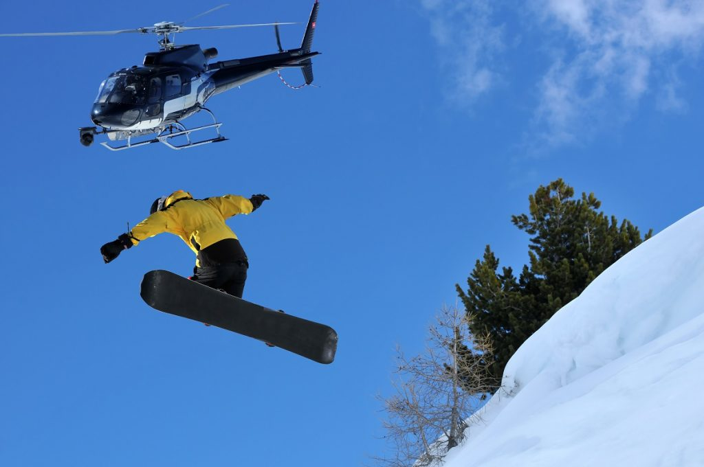 man jumping off a helicopter to snowboard