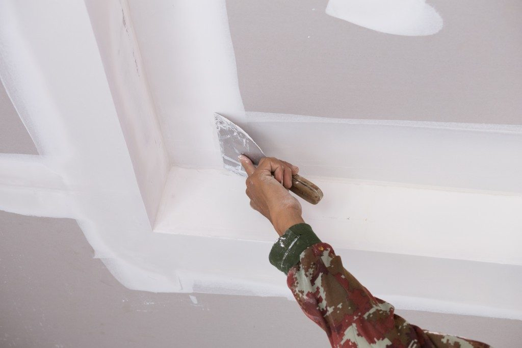 man placing plaster on ceiling