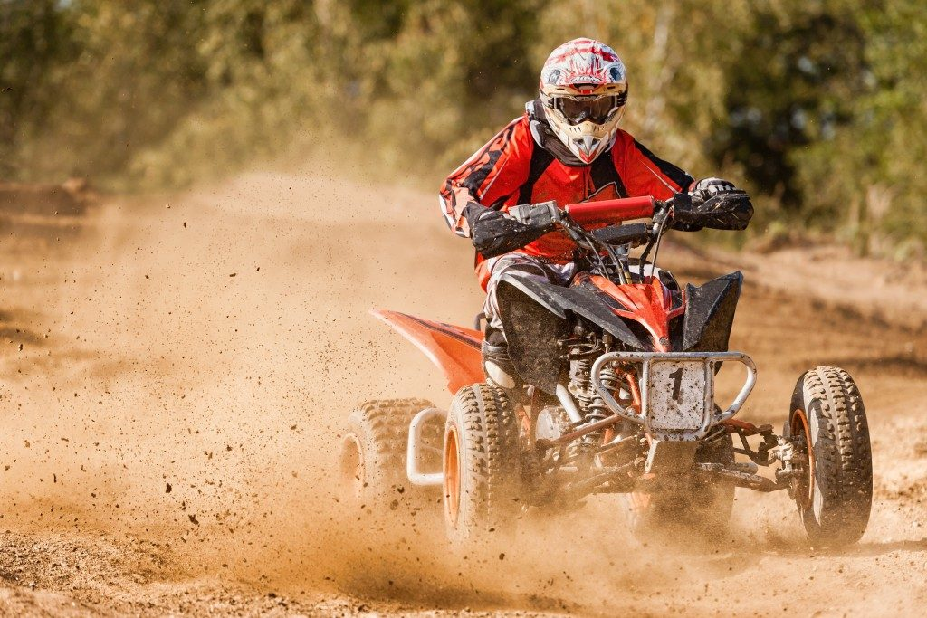 Man riding ATV on dirt road