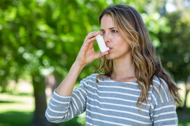 Woman taking her inhaler because of asthma