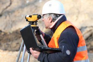 man holsing a laptop, land surveying