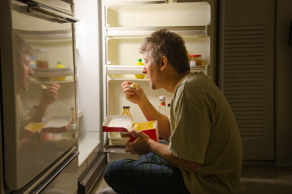 Man eating in front of the refrigerator