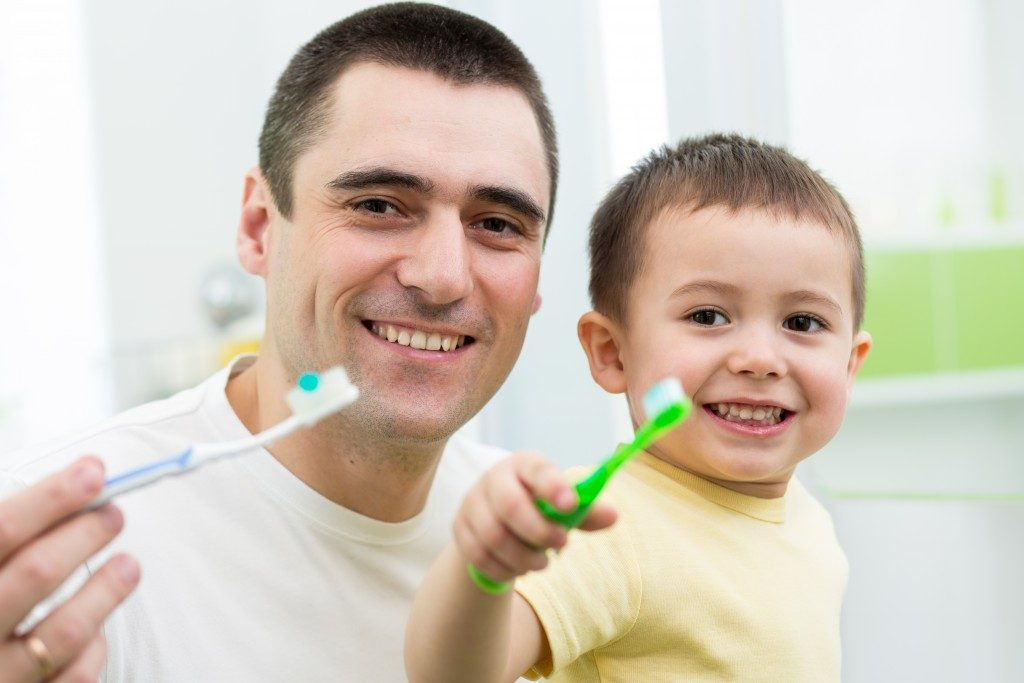 father and son brushing his teeth