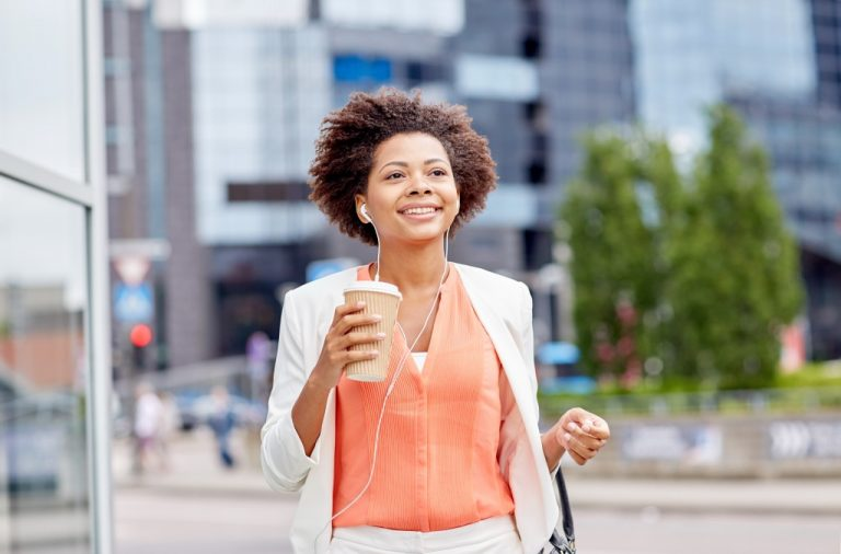 working woman walking confidently with coffee and music