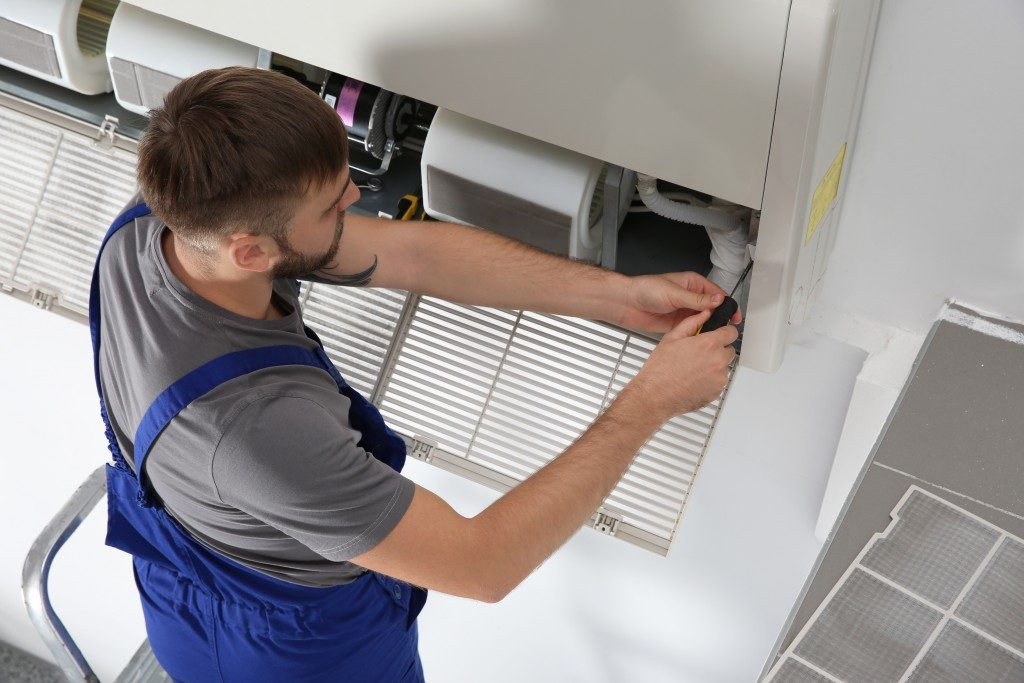 man repairing an AC unit