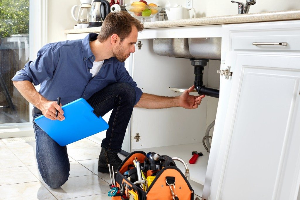repairman fixing sink pipes