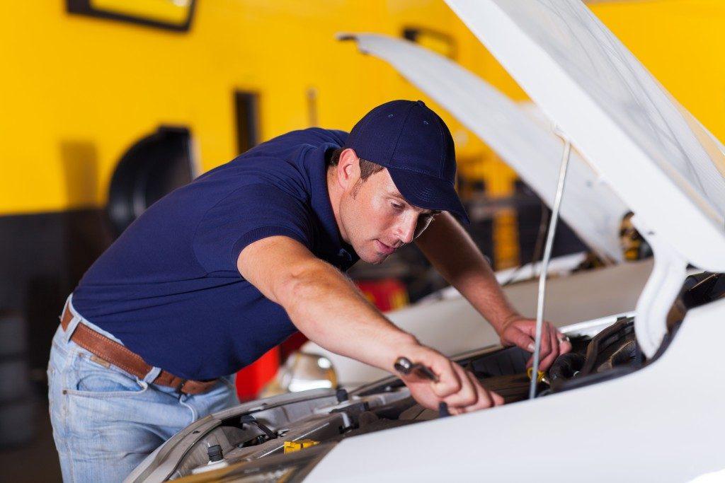auto mechanic repairing vehicle at the shop