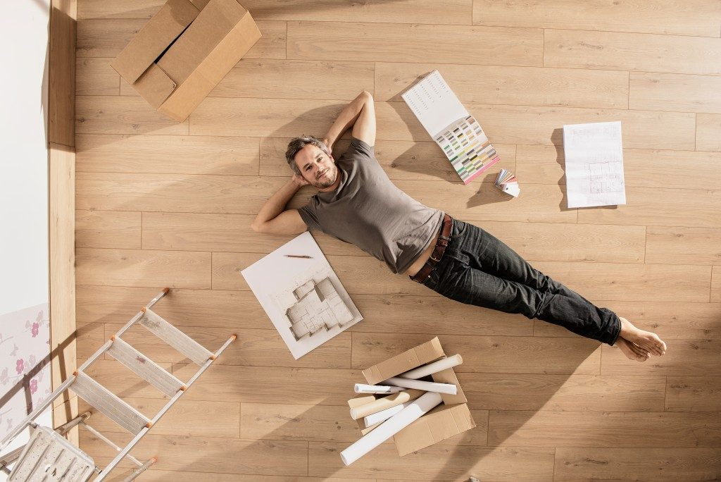 man laying on the floor of an empty room for renovation