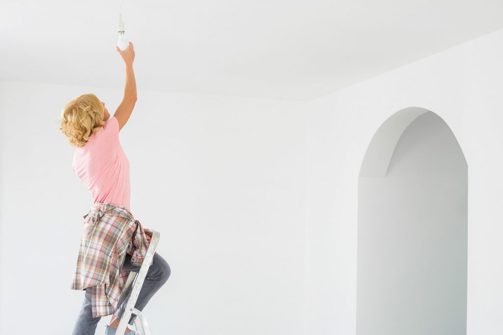woman changing the light bulb