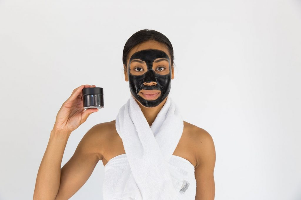 woman holding charcoal mask