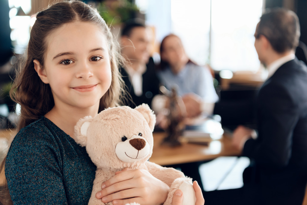 Little girl smiling with a teddy bear