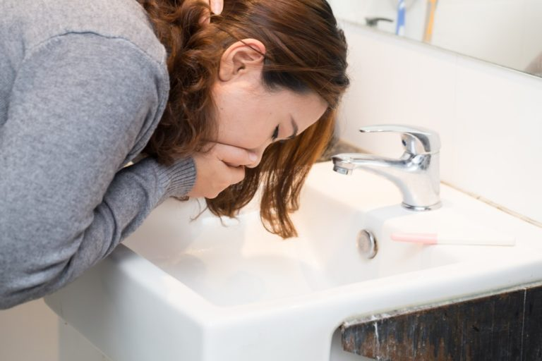 woman vomiting in the bathroom
