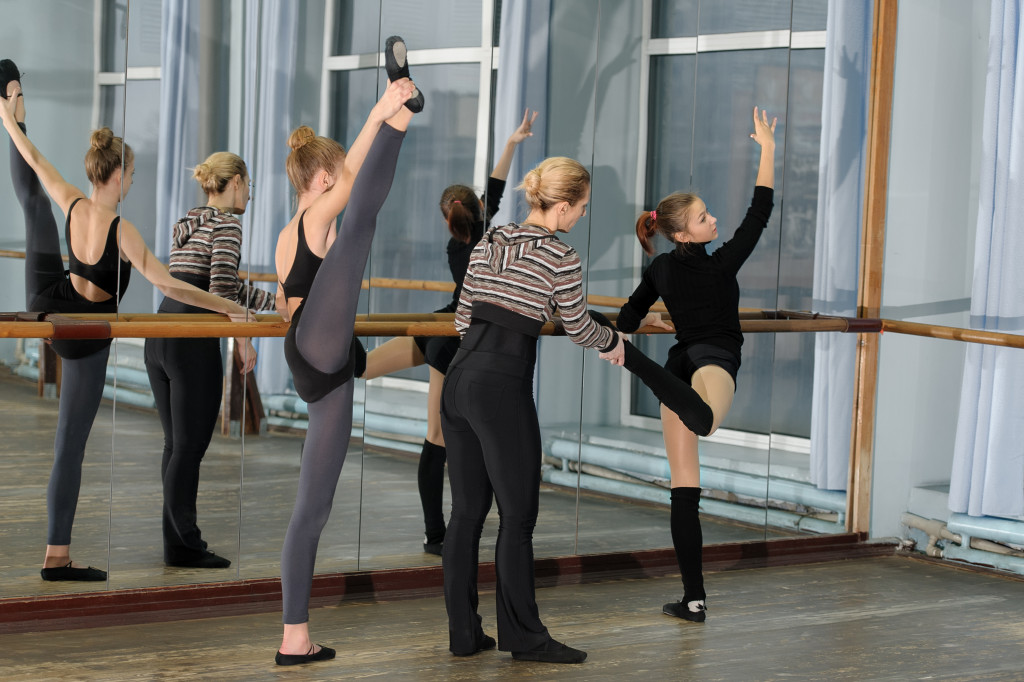 Choreographer helping young ballet dancer to have right position