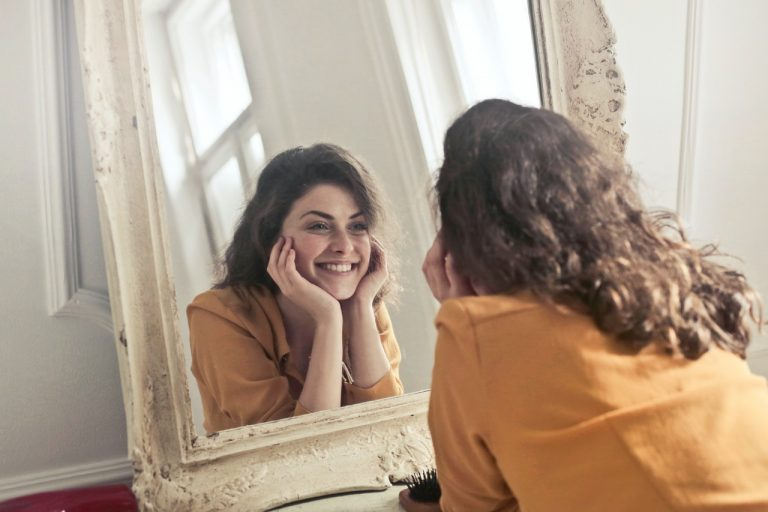 woman smiling facing the mirror