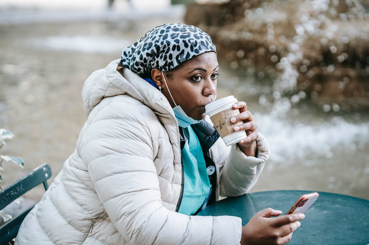 woman drinking coffee at a park