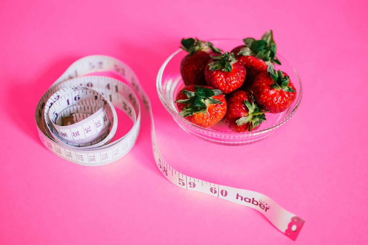 bowl of strawberries and measuring tape