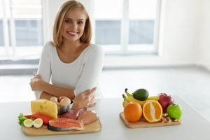 woman standing by the counter with fruit in it