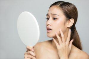 woman shocked looking at mirror